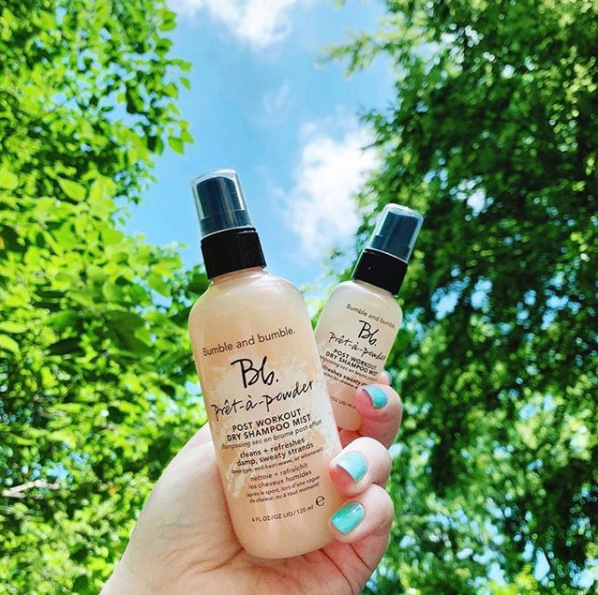 Hand holding two Bb products; trees and sky in background
