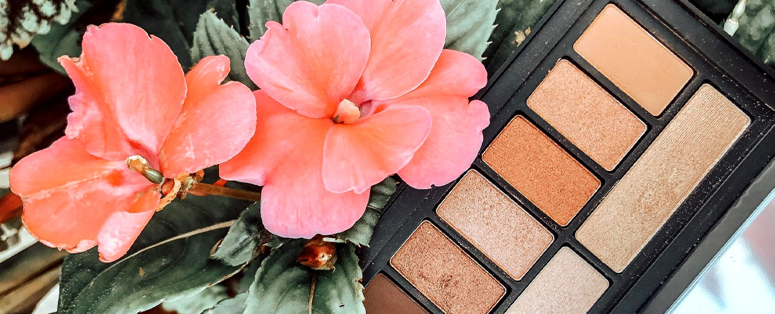 Brown and gold eyeshadow palette next to pink flowers